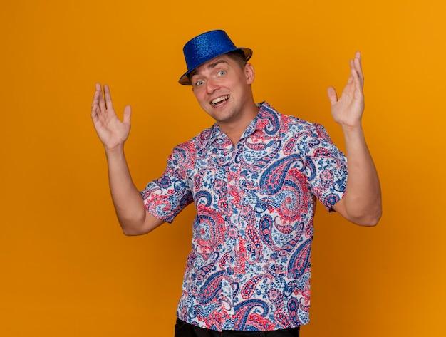 Glimlachende jonge partijkerel die blauwe hoed draagt die handen uitspreidt die op sinaasappel worden geïsoleerd