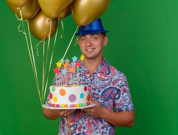 Glimlachende jonge partijkerel die de blauwe ballons van de hoedenholding met cake draagt die op groen wordt geïsoleerd