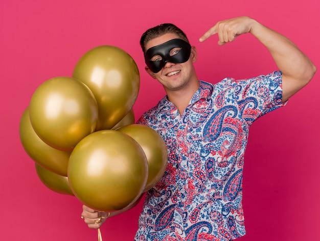 Glimlachende jonge partijkerel die de holdings van het maskeradeoogmasker draagt en wijst op ballons die op roze worden geïsoleerd