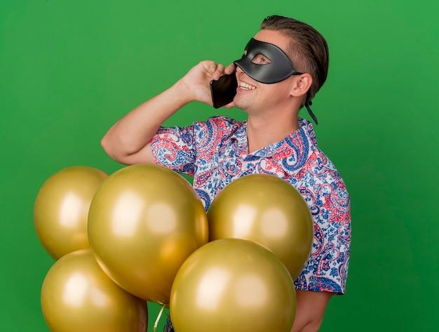 Glimlachende jonge partijkerel die kant bekijkt die maskeradeoogmasker draagt dat zich tussen ballons bevindt en op telefoon spreekt die op groen wordt geïsoleerd