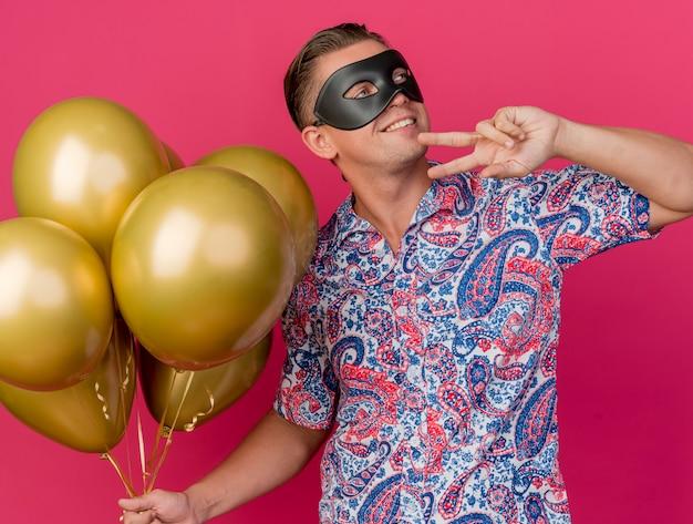 Glimlachende jonge partijkerel die kant bekijkt die maskeradeoogmasker houdt die ballons houdt en vredesgebaar toont dat op roze wordt geïsoleerd