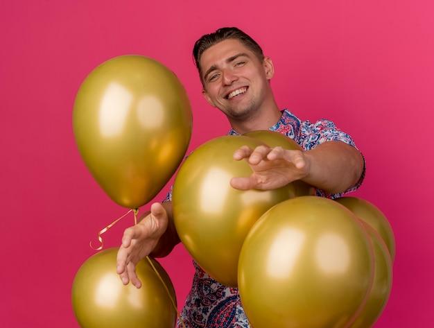 Glimlachende jonge partijkerel die kleurrijk overhemd draagt dat zich achter ballons houdt die handen uitsteken die op roze worden geïsoleerd