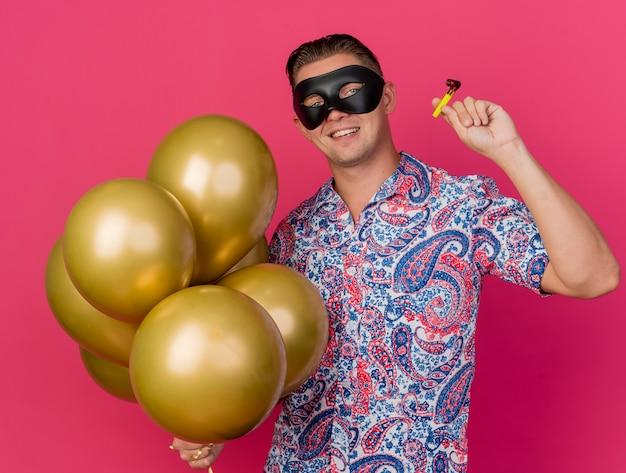 Glimlachende jonge partijkerel die maskeradeoogmasker draagt die ballons met partijblazer houdt die op roze wordt geïsoleerd