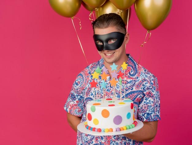 Glimlachende jonge partijkerel die maskeradeoogmasker draagt die zich voor ballons bevindt en cake houdt die op roze wordt geïsoleerd