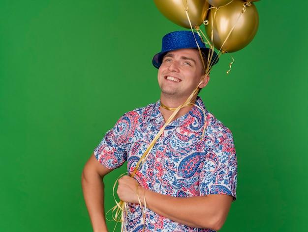 Glimlachende jonge partijkerel die omhoog het dragen van blauwe de ballons van de hoedholding kijkt die om hals worden gebonden die op groen wordt geïsoleerd