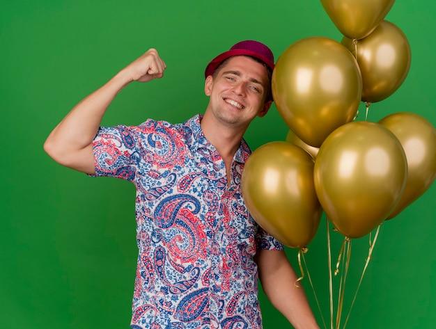 Glimlachende jonge partijkerel die roze hoed draagt ?? die ballons houdt en sterk gebaar toont dat op groene achtergrond wordt geïsoleerd