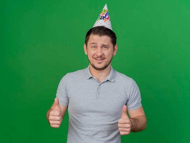 Glimlachende jonge partijkerel die verjaardag glb draagt die duimen toont die omhoog op groen worden geïsoleerd