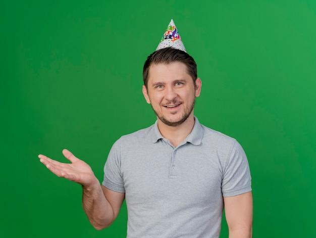 Glimlachende jonge partijkerel die verjaardagsglb-punten met hand aan kant draagt die op groen wordt geïsoleerd