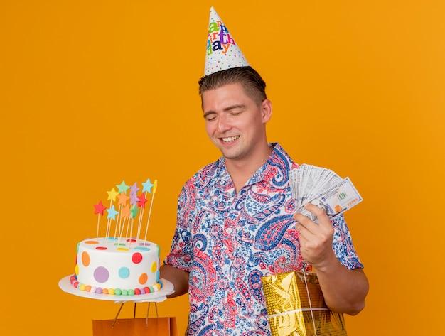Glimlachende jonge partijkerel met gesloten ogen die verjaardag glb dragen die cake met giften en geld houden die op oranje wordt geïsoleerd