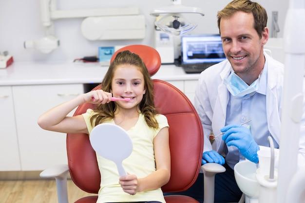 Glimlachende jonge patiënt met een tandarts in tandkliniek