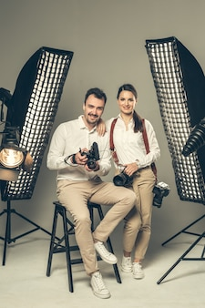 Glimlachende jonge professionele fotografen die in de studio stellen
