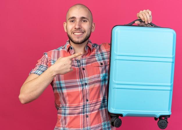 Glimlachende jonge reiziger man houden en wijzend op koffer geïsoleerd op roze muur met kopie ruimte