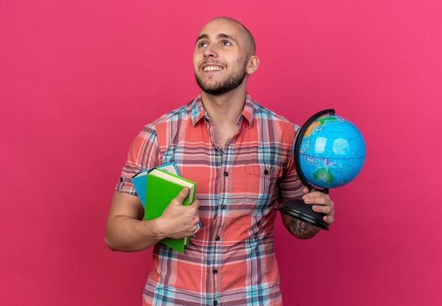 Glimlachende jonge reiziger man met boeken en globe kijkend naar kant geïsoleerd op roze muur met kopieerruimte