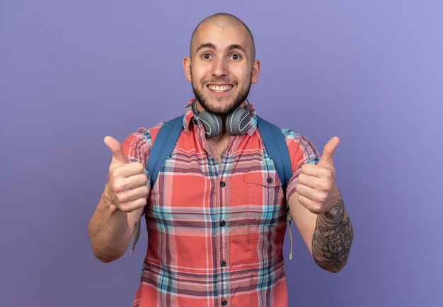 Glimlachende jonge reiziger man met koptelefoon om zijn nek en met rugzak duimen omhoog geïsoleerd op paarse muur met kopieerruimte
