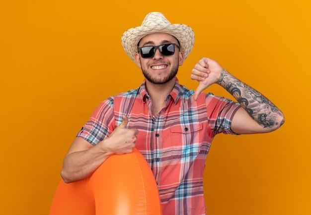 Glimlachende jonge reiziger man met stro strand hoed in zonnebril met zwemring duimen omhoog en duim omlaag geïsoleerd op oranje muur met kopie ruimte
