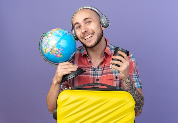 Glimlachende jonge reiziger man op koptelefoon met globe en papieren beker staande achter koffer geïsoleerd op paarse muur met kopieerruimte