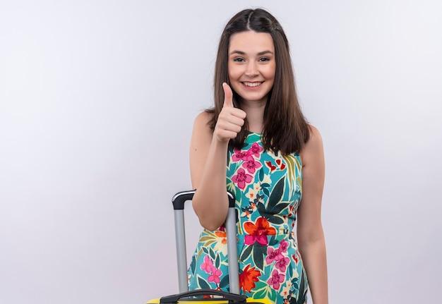 Glimlachende jonge reizigersvrouw die duim met koffer op geïsoleerde witte muur tonen