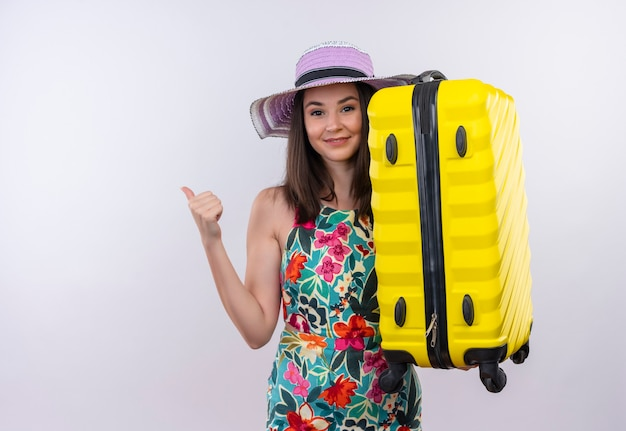 Glimlachende jonge reizigersvrouw die duim tonen die koffer op geïsoleerde witte muur houden
