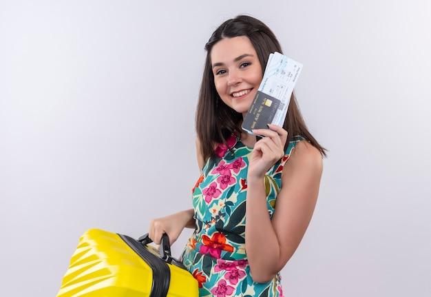 Glimlachende jonge reizigersvrouw die veelkleurige kleding draagt die een mobiele zak en kaartjes op witte muur houdt