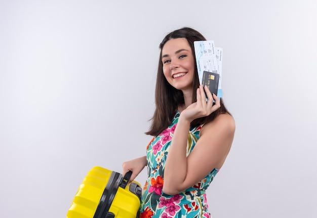Glimlachende jonge reizigersvrouw met vliegtuigtickets en koffer op geïsoleerde witte muur
