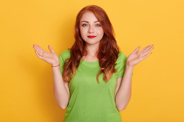 Glimlachende jonge rode vrouw in vrijetijdskleding poseren geïsoleerd, vrouwelijke spreidende handen opzij
