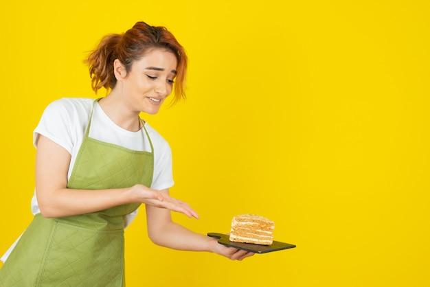 Glimlachende jonge roodharige die een plakje cake vasthoudt en de hand erop wijst