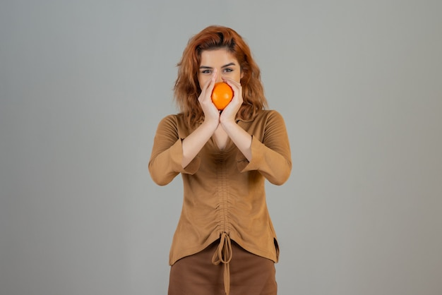Glimlachende jonge roodharige die met beide handen verse sinaasappel vasthoudt en naar de camera kijkt.