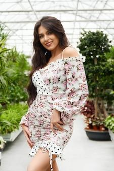 Glimlachende jonge schattige vrouw poseren in de buurt van groene planten