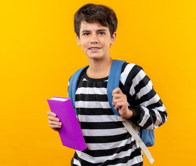 Glimlachende jonge schooljongen die een rugzak draagt met een boek dat op een oranje muur wordt geïsoleerd