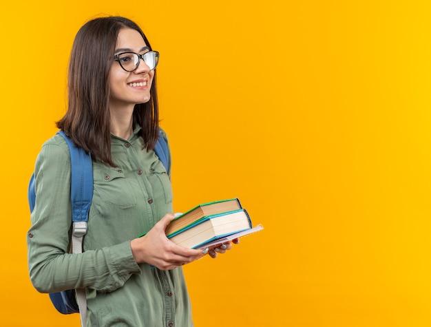 Glimlachende jonge schoolvrouw die een rugzak draagt met een bril die boeken vasthoudt