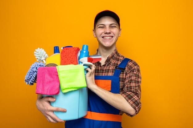 Glimlachende jonge schoonmaakster die een uniform draagt en een pet met een emmer schoonmaakgereedschap vasthoudt