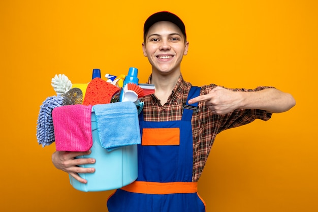 Glimlachende jonge schoonmaakster met uniform en pet die vasthoudt en wijst naar emmer met schoonmaakgereedschap