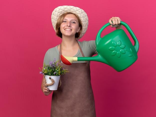 Glimlachende jonge slavische vrouwelijke tuinman die tuinierhoed draagt die bloemen in bloempot met gieter water geeft die op roze muur met exemplaarruimte wordt geïsoleerd