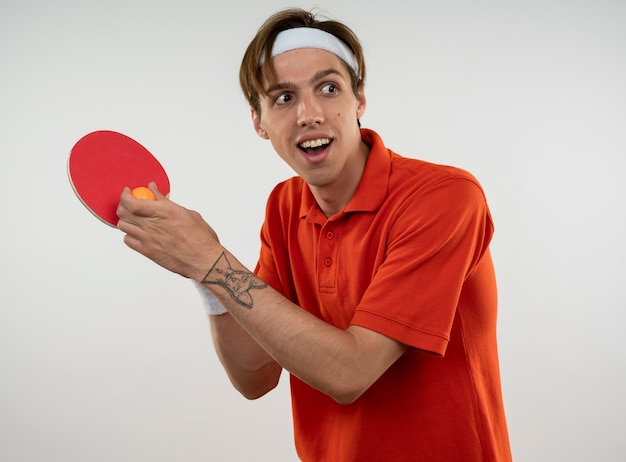 Glimlachende jonge sportieve kerel die hoofdband met de pingpongracket van de manchetholding met bal draagt