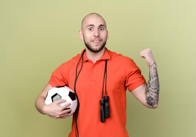 Glimlachende jonge sportieve man met bal met springtouw op schouder en ja gebaar geïsoleerd op olijfgroene muur tonen