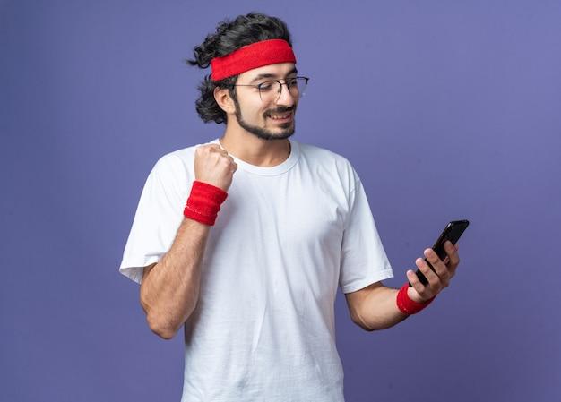 Glimlachende jonge sportieve man met een hoofdband met een polsband die vasthoudt en naar de telefoon kijkt met een ja-gebaar