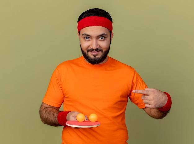 Glimlachende jonge sportieve man met hoofdband en polsbandje houden en wijst op pingpongracket met ballen geïsoleerd op olijfgroene achtergrond