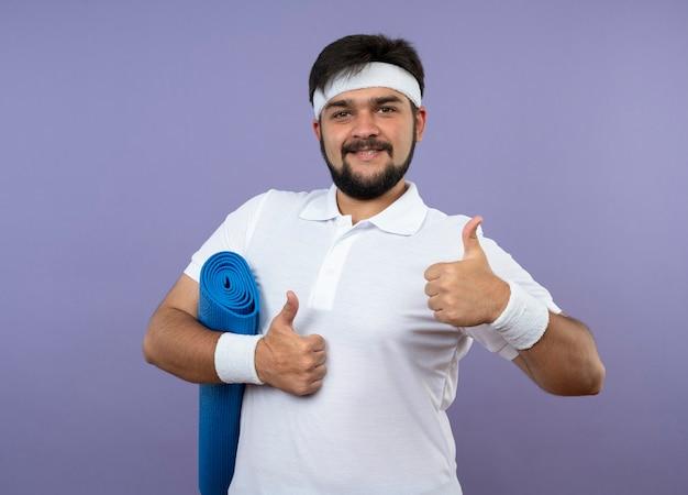 Glimlachende jonge sportieve man met hoofdband en polsbandje houden yogamat duimen opdagen