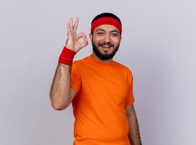 Glimlachende jonge sportieve man met hoofdband en polsbandje met ok gebaar geïsoleerd op wit