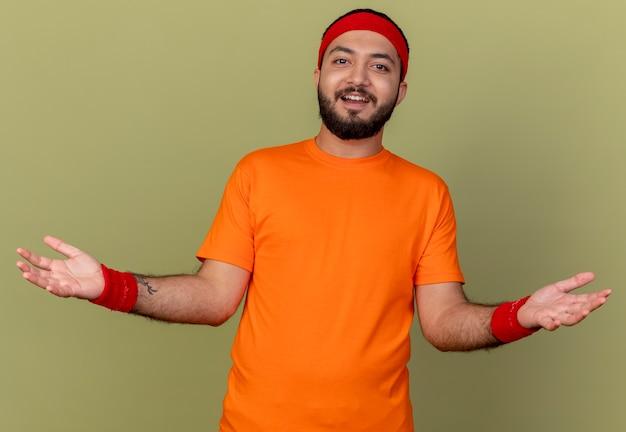 Glimlachende jonge sportieve man met hoofdband en polsbandje spreidende handen geïsoleerd op olijfgroene achtergrond