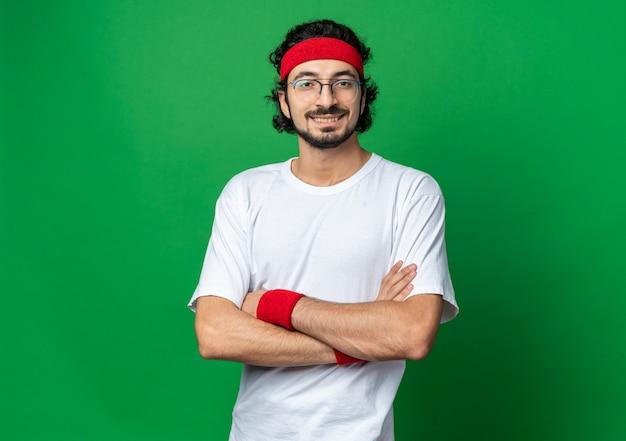 Glimlachende jonge sportieve man met hoofdband met polsband die handen kruist