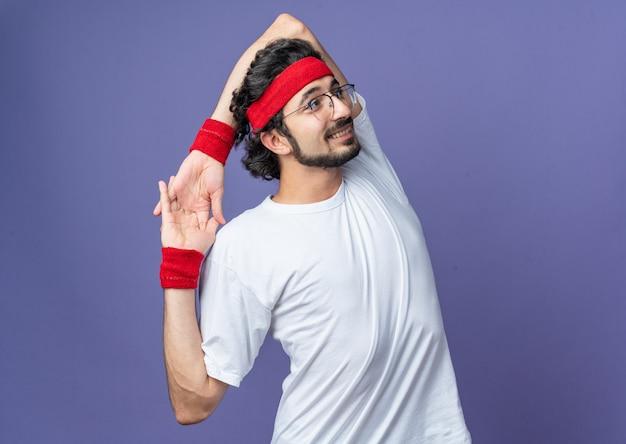 Glimlachende jonge sportieve man met hoofdband met polsband die zijn arm uitstrekt