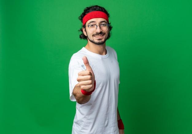 Glimlachende jonge sportieve man met hoofdband met polsbandje duim opdagen