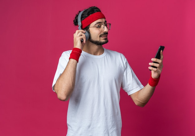Glimlachende jonge sportieve man met hoofdband met polsbandje en koptelefoon die de telefoon vasthoudt en bekijkt