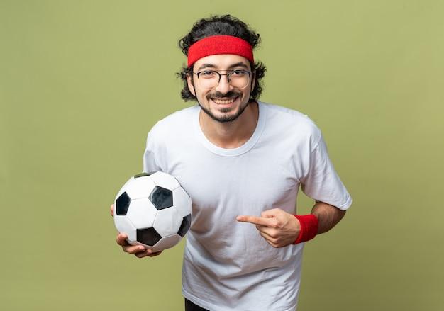 Glimlachende jonge sportieve man met hoofdband met polsbandje en wijst naar bal