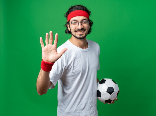 Glimlachende jonge sportieve man met hoofdband met polsbandje met bal die stopgebaar toont