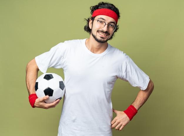 Glimlachende jonge sportieve man met hoofdband met polsbandje met bal en hand op heup