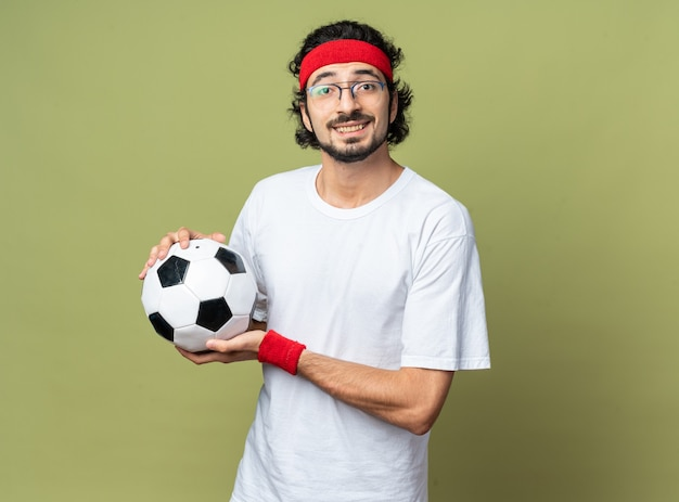 Glimlachende jonge sportieve man met hoofdband met polsbandje met bal