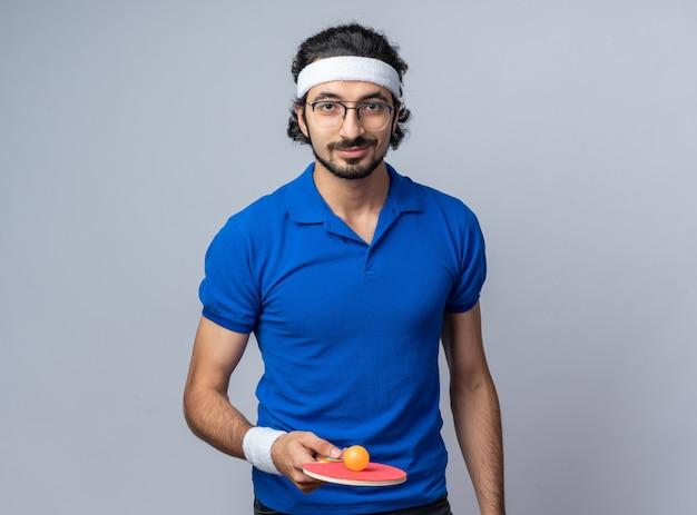 Glimlachende jonge sportieve man met hoofdband met polsbandje met pingpongbal op racket
