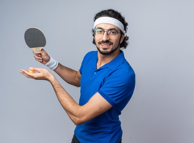 Glimlachende jonge sportieve man met hoofdband met polsbandje met pingpongracket met bal